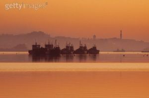 Travel. Editorial image. Fishing boats at sunset in Larache Harbour Marocco.