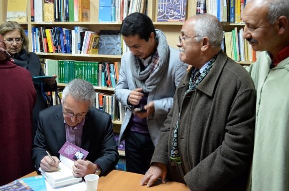 Firmando ejemplares para Aziz Bouhdoud, junto a Mohamed Mrabet y Abdeslam Boubel